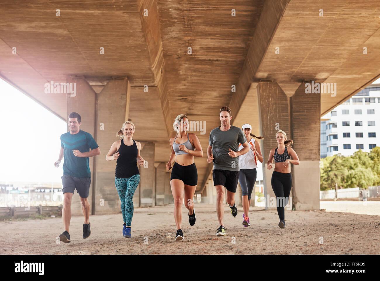 Gruppe von Athleten, die auf einer Straße unter der Brücke in der Stadt. Junge Männer und Frauen Stockbild