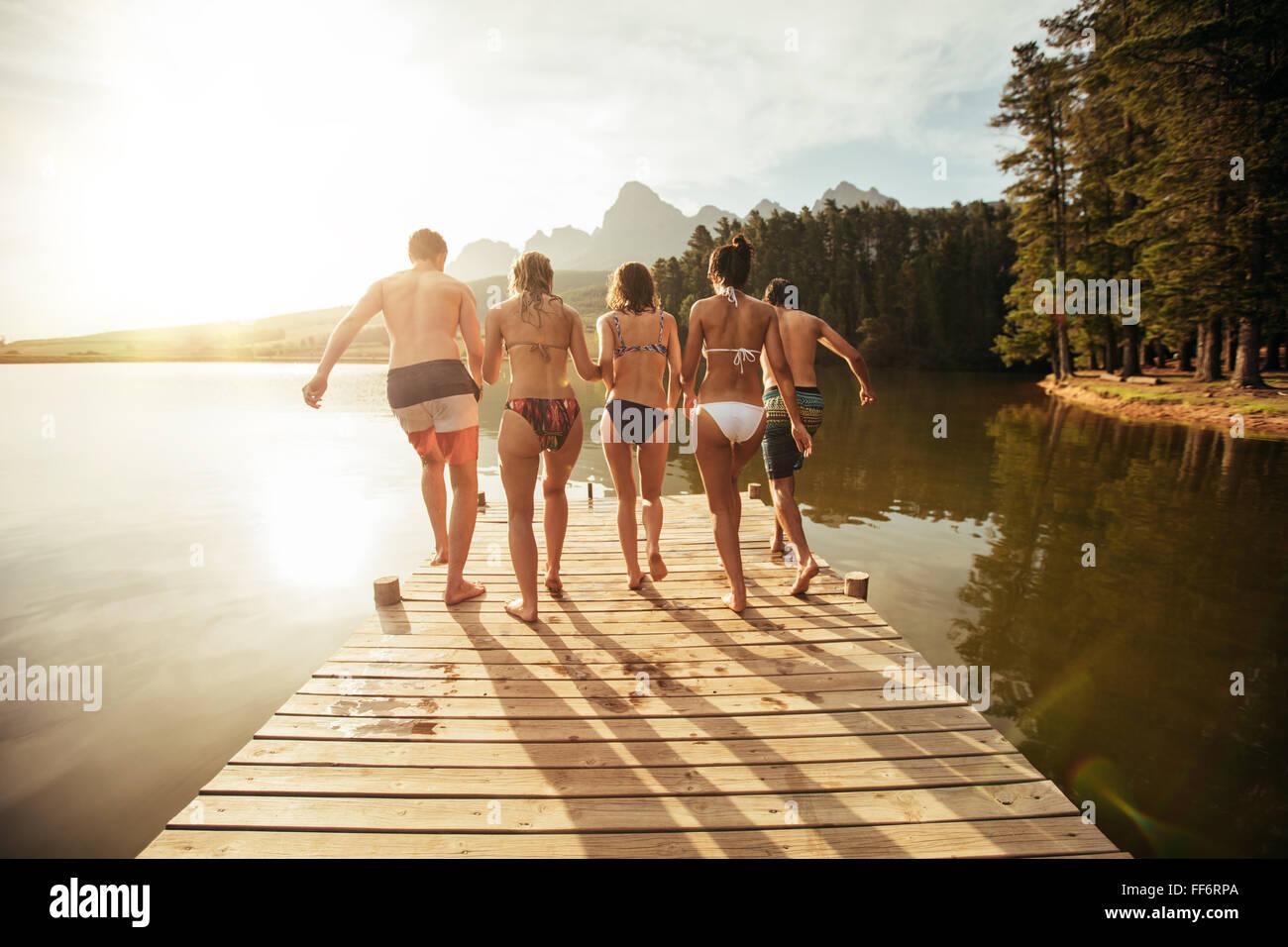 Porträt von jungen Freunden sich an einem sonnigen Tag in den See springen. Junge Menschen laufen auf einem Stockbild