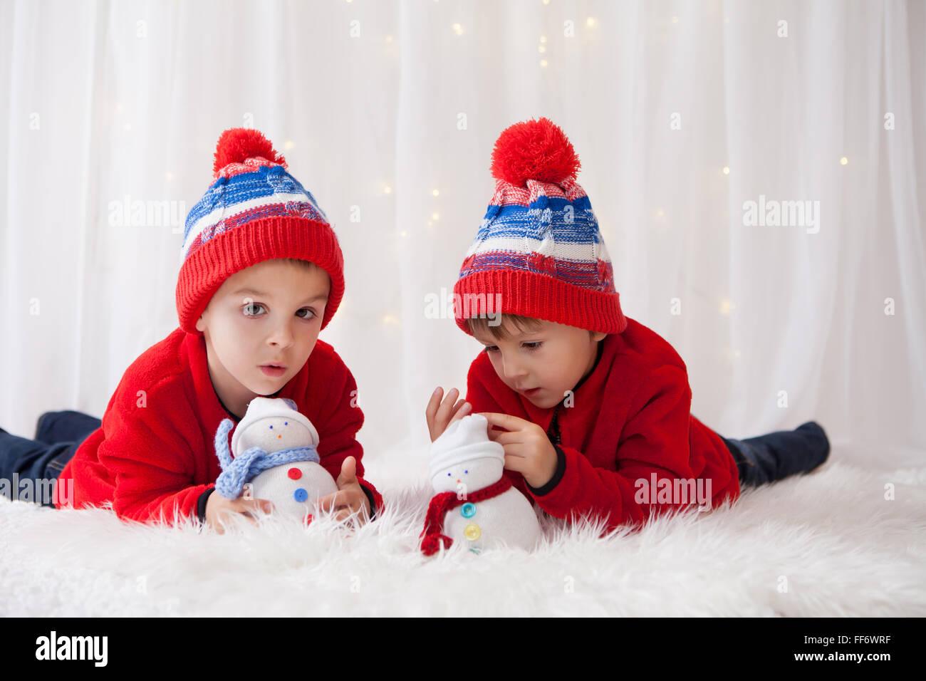 Süße Kinder, Bruder Jungen spielen mit handgefertigten Schneemänner zu Hause Weihnachtsbeleuchtung Stockbild