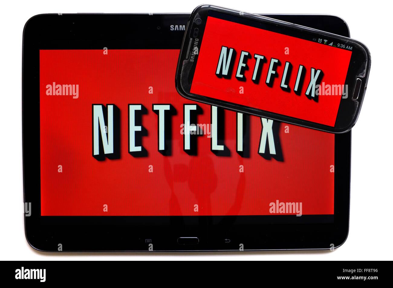 Die Netflix-Logo auf einem Smartphonebildschirm und ein Tablet vor weißem Hintergrund fotografiert. Stockbild