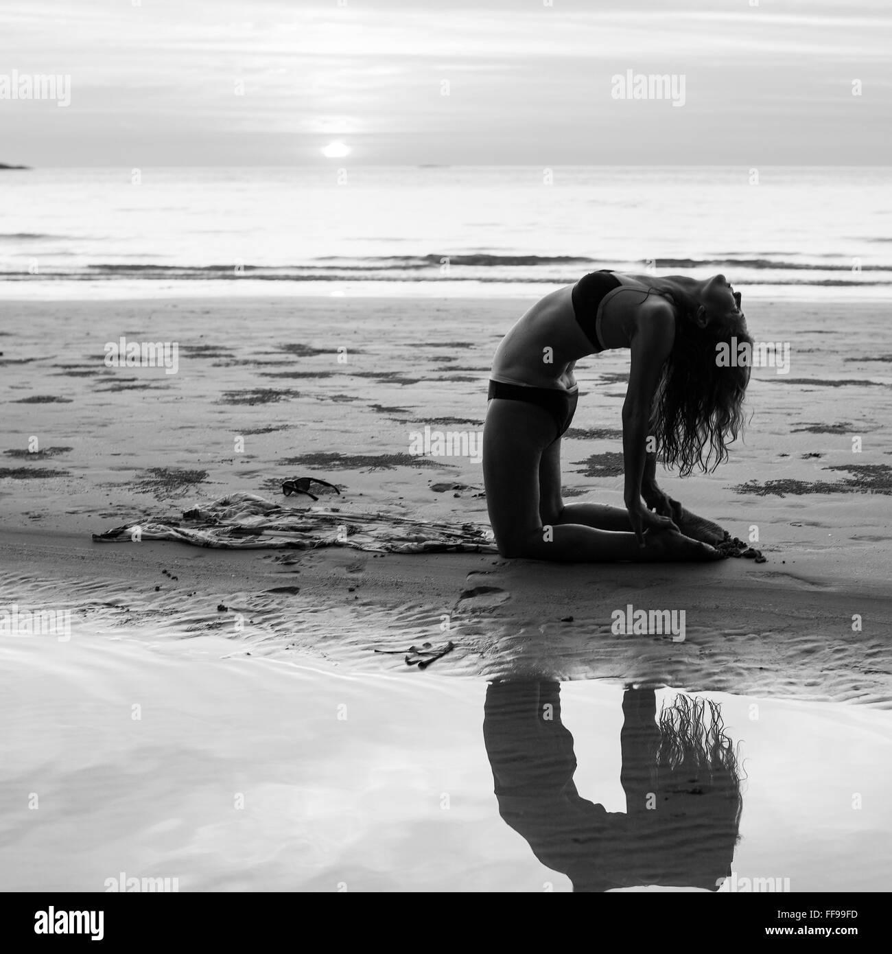 frau silhouette yoga bungen am strand bei sonnenuntergang schwarz wei fotografie stockfoto. Black Bedroom Furniture Sets. Home Design Ideas