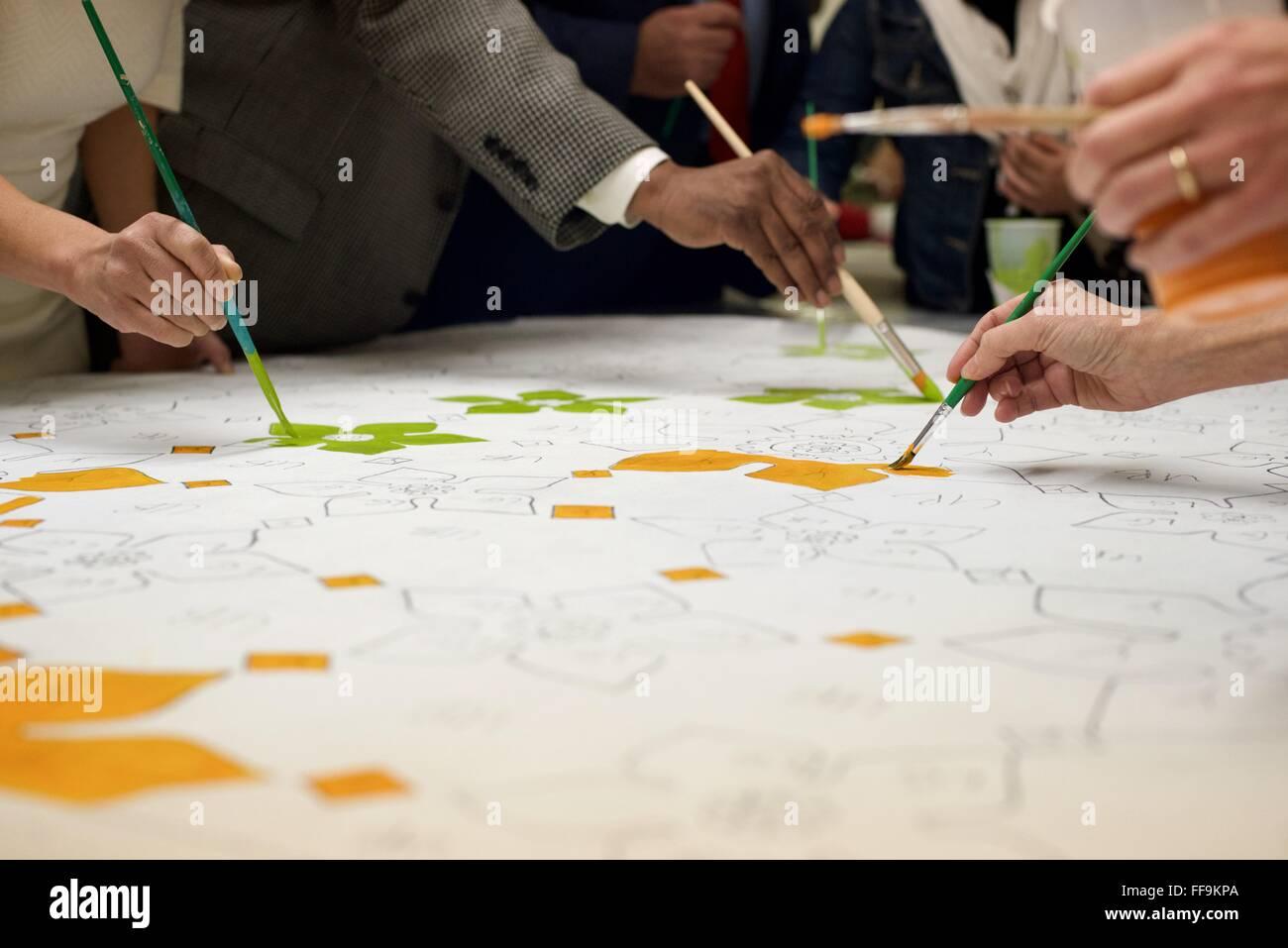 Community-Mitglieder helfen in den dekorativen Elementen des was Teile eines Wandbildes vor einer Moschee North Stockbild
