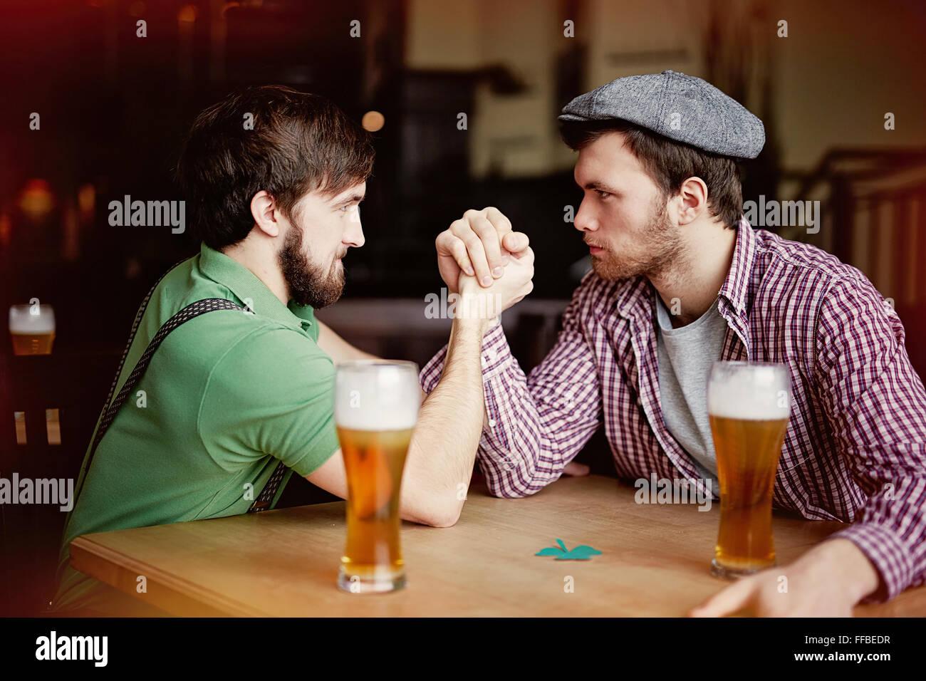 Zwei junge Männer sitzen in der Kneipe Armdrücken Stockbild
