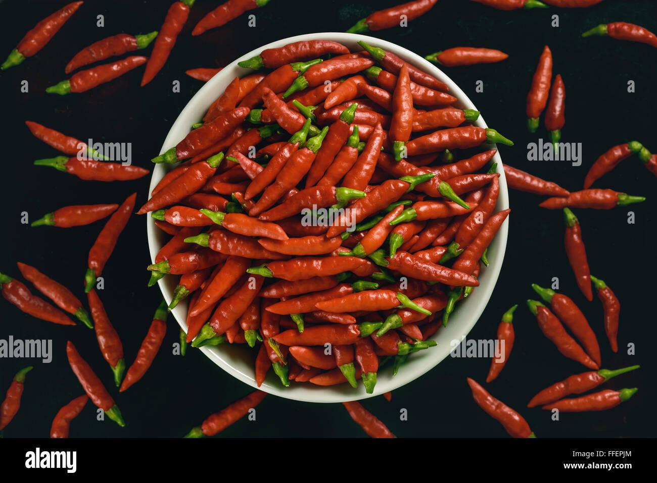 Rote Paprika in Schüssel auf schwarzem Hintergrund. Stockbild