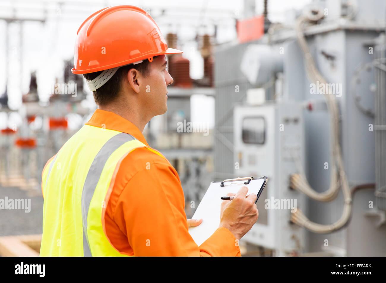 Seitenansicht der Elektroingenieur schreiben in Zwischenablage im Umspannwerk Stockbild