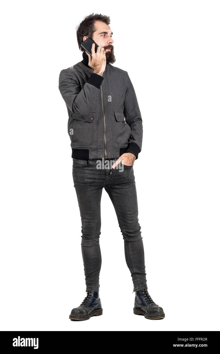 Coole Hipster tragen Jacke und Militärstiefel sprechen auf dem Handy wegsehen. Ganzkörper-Länge isoliert Stockbild