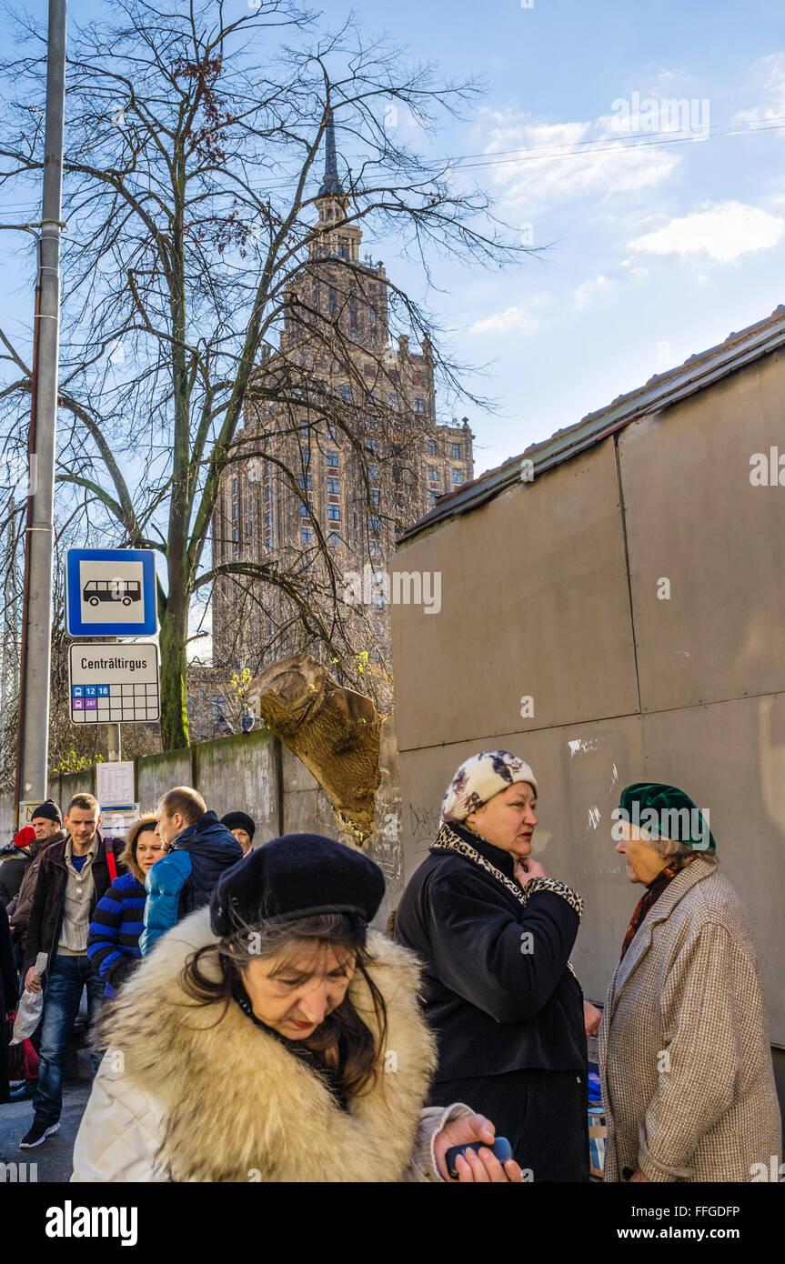 Lettische Frauen auf einen israelischen Bus stop mit der Akademie der Wissenschaften sowjetischen Gebäude im Stockbild