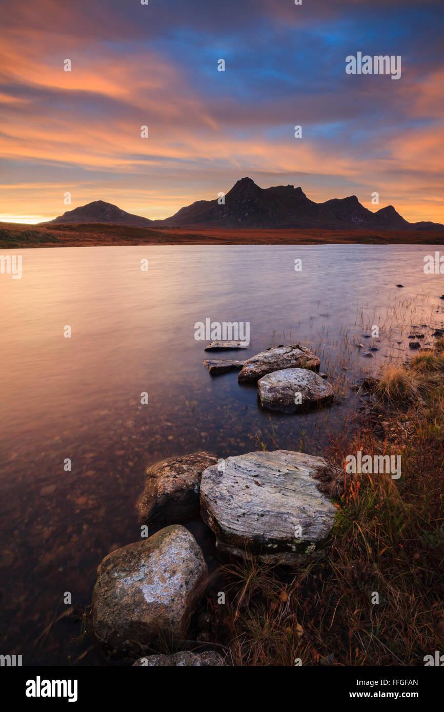 Felsen am Ufer von Loch Hakel erfasst bei Sonnenaufgang Anfang November mit Ben Loyal in der Ferne. Stockbild