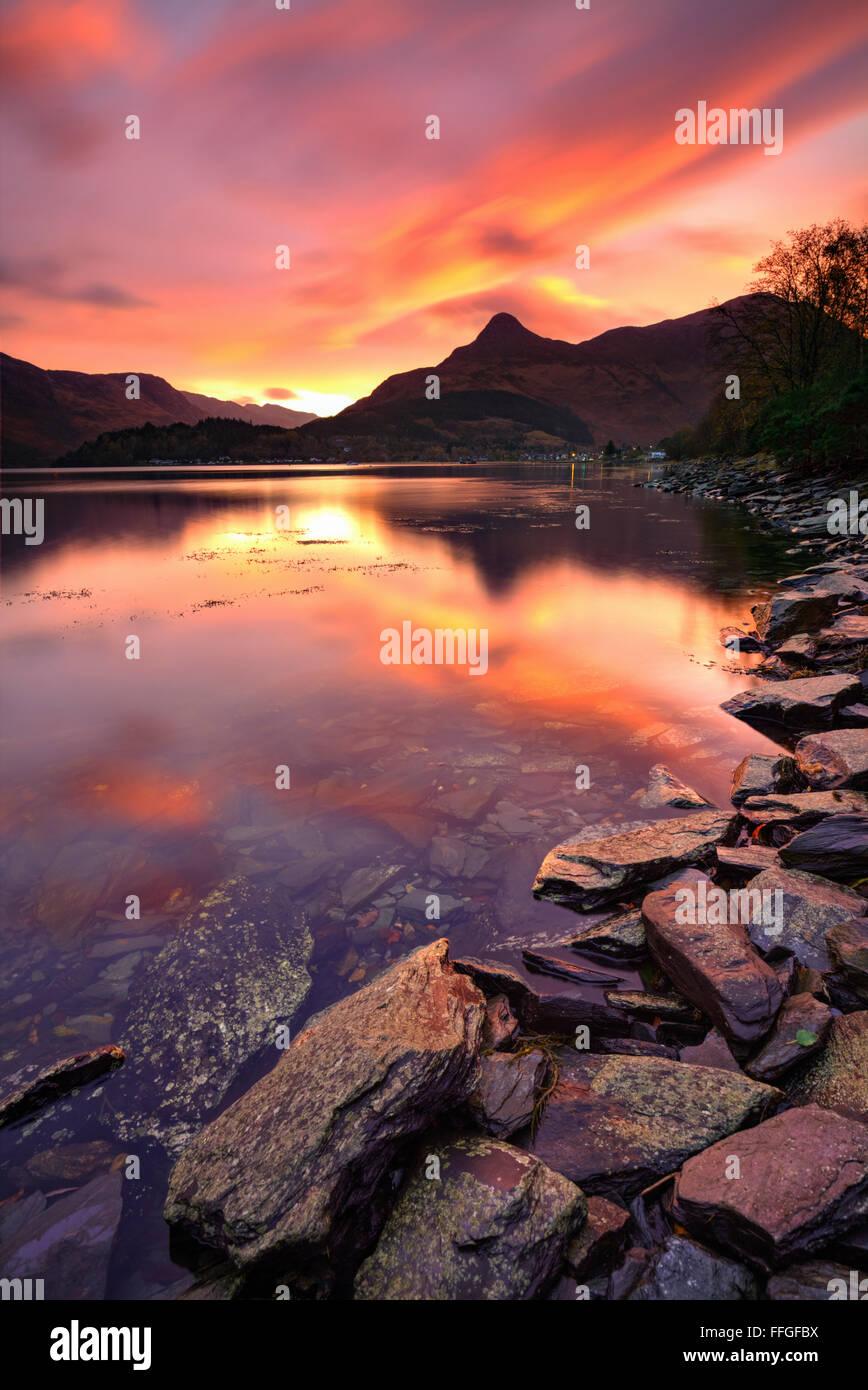 Die Pap Glencoe in den schottischen Highlands, spiegelt sich in Loch Leven bei Sonnenaufgang Anfang November. Stockbild