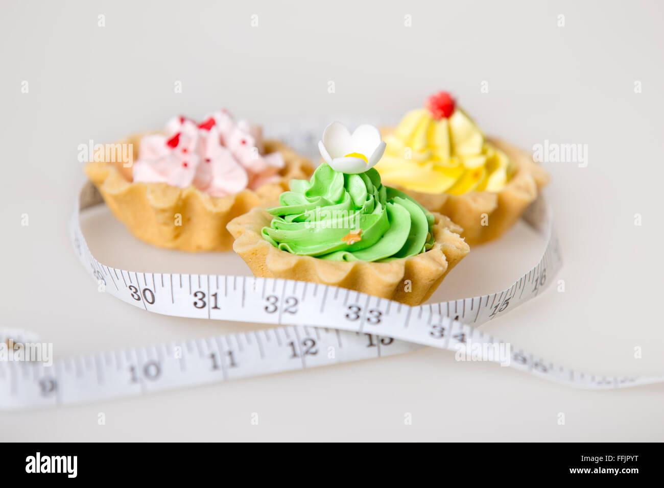 Drei bunte grüne, rosa und gelbe Torte Kuchen verpackt in Maßband auf weißem Hintergrund, ungesunden Stockbild