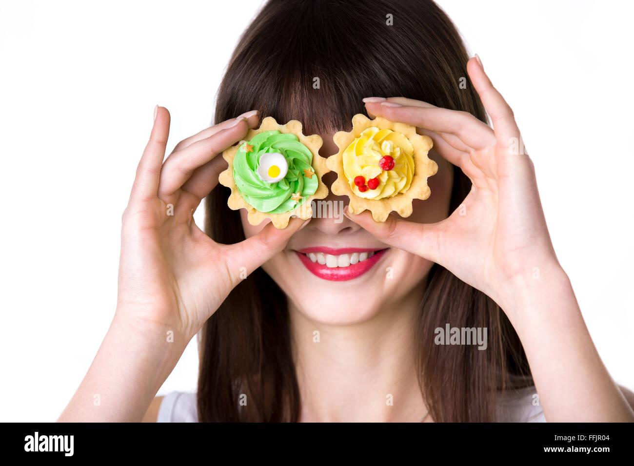 Kopfschuss Porträt junge lächelnde Frau mit zwei herben Sahnetorten in Teig Körbe, herumalbern, mit Keksen als Augen Stockfoto