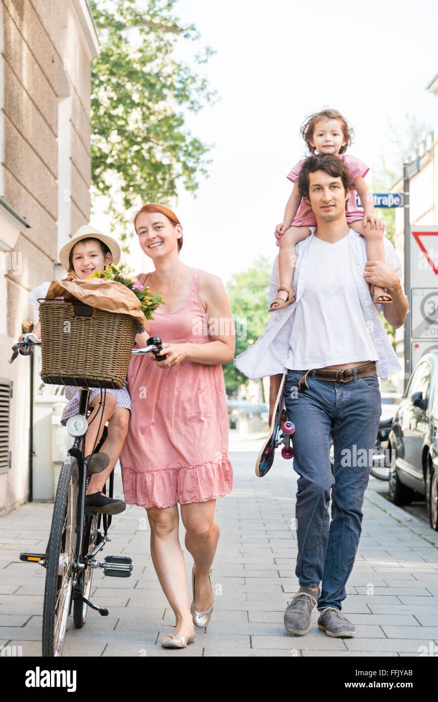 Familie mit zwei Kindern, die zu Fuß in die Stadt Stockbild
