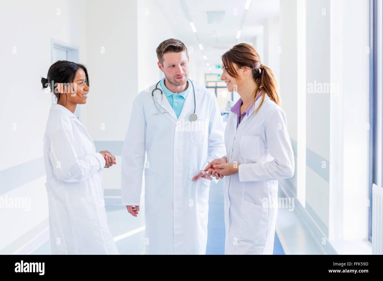 Arzt und Mitarbeiter sprechen im Krankenhausflur Stockbild