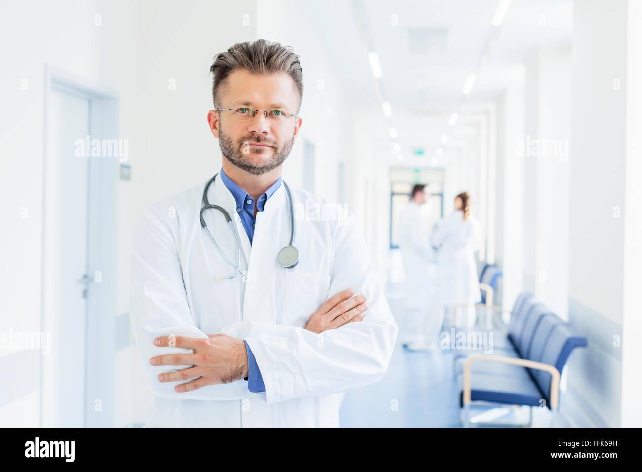 Porträt des Arztes mit verschränkten im Krankenhausflur Stockbild