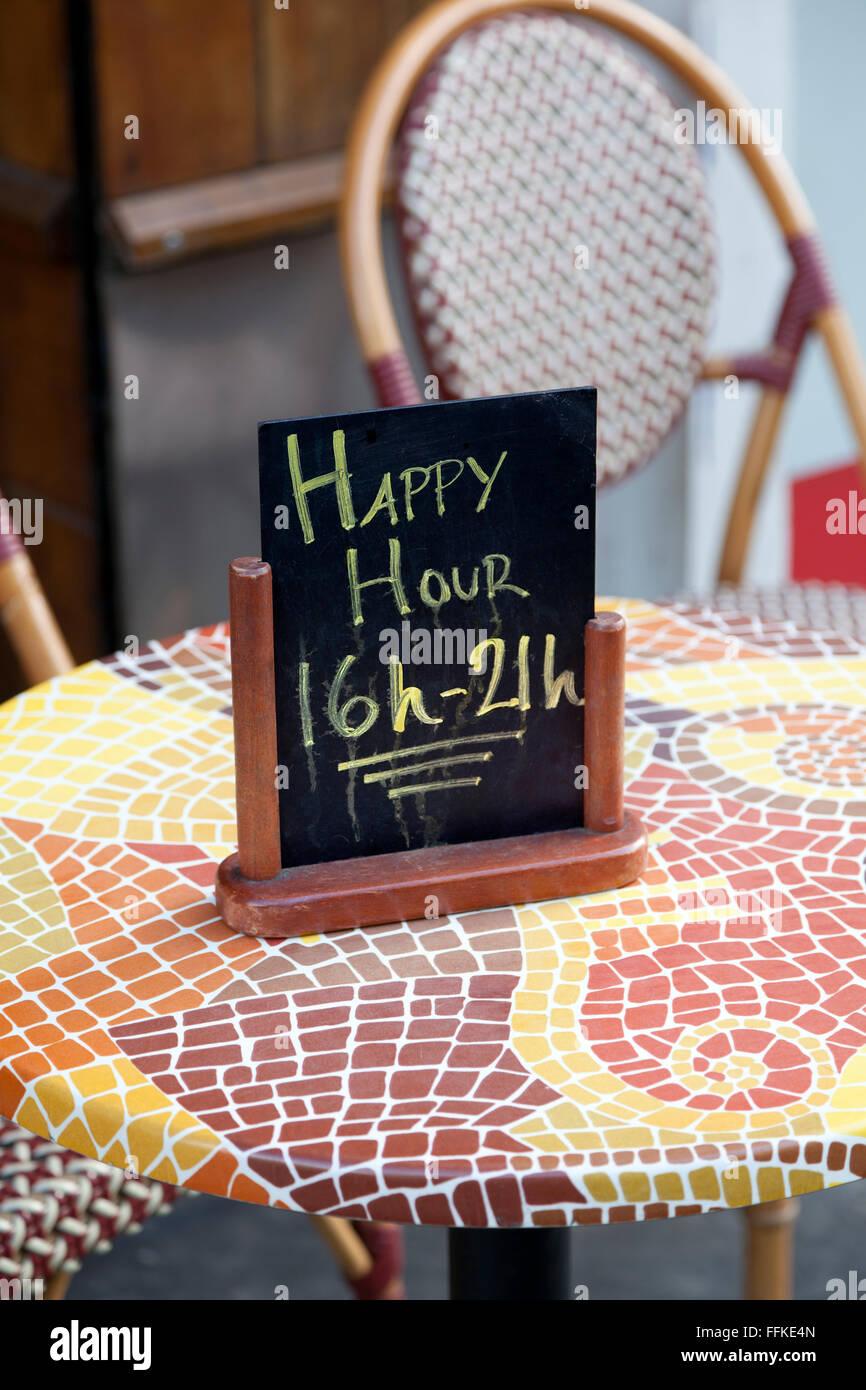 Melden Sie für glückliche Stunden auf einem Tisch Stockbild