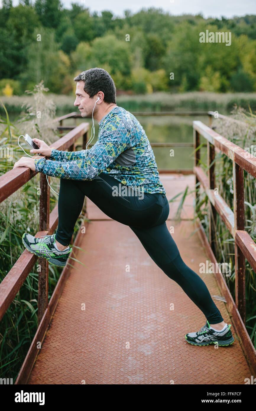 Läufer auf rostigen Brücke Dehnung gegen die grüne Natur Stockbild
