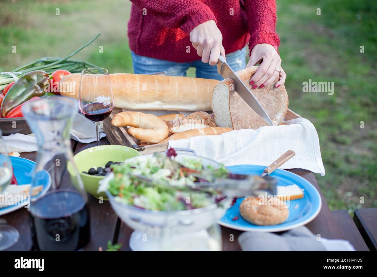 Person auf Gartenparty Laib Brot schneiden Stockbild