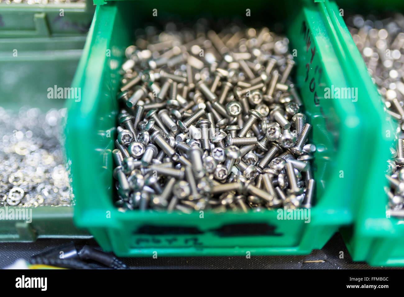 Schrauben in einer grünen Box in einer Elektronik-Fabrik Stockbild