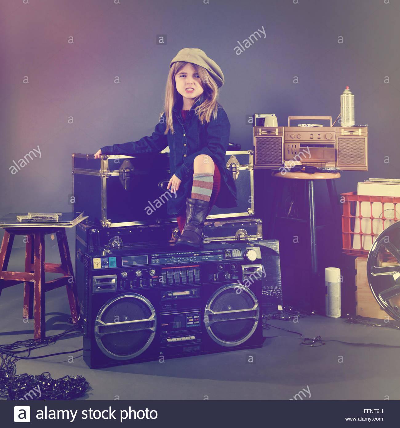 Ein cooles Kind steht vor dem Musikhintergrund mit 80er Jahre Stereo, Aufzeichnungen und Retro-Kassetten. Stockbild