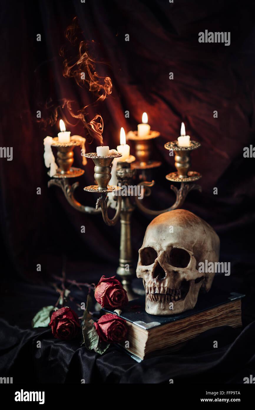 Stillleben mit Totenkopf, Buch und Kerze Stockbild