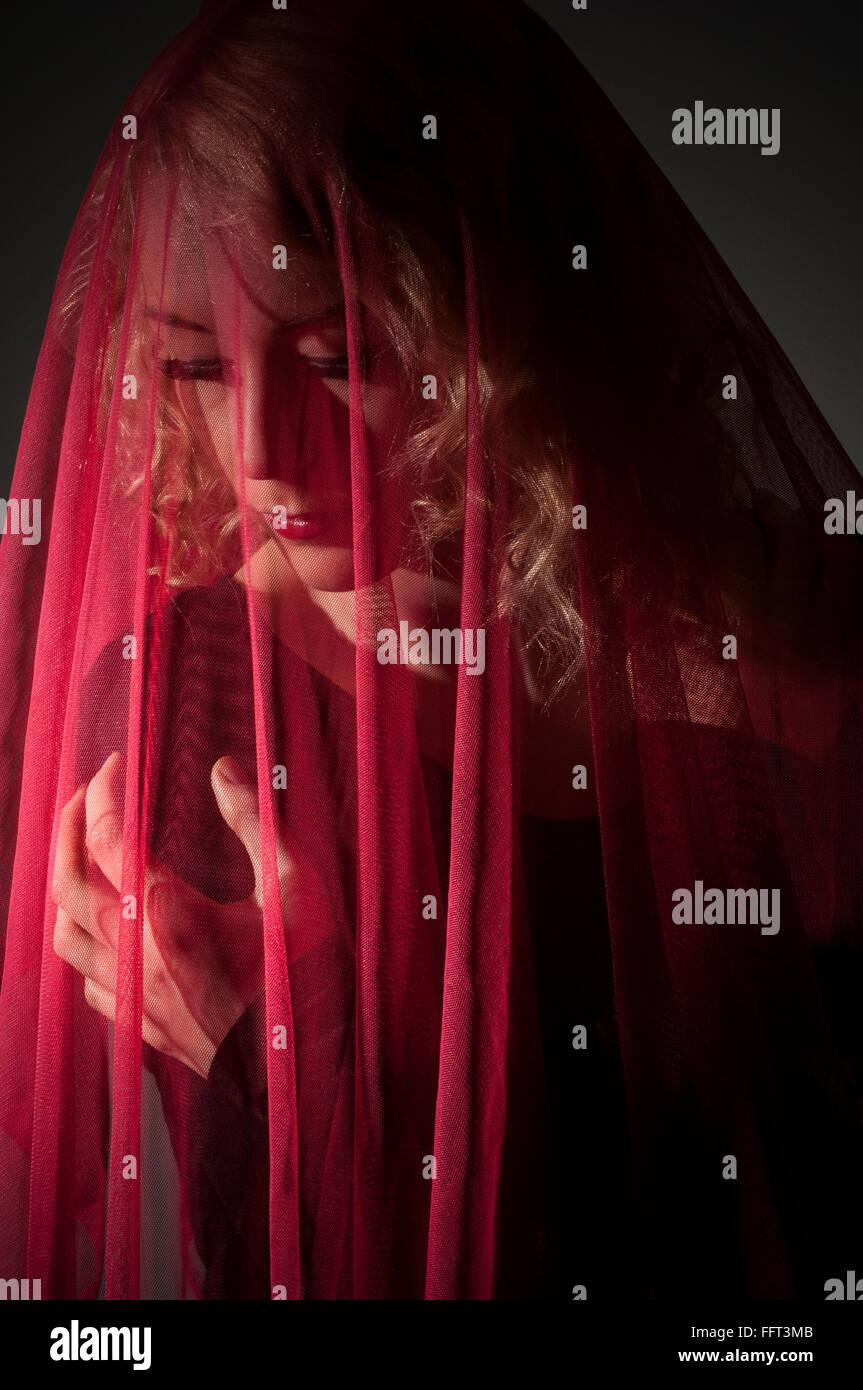 Frau bedeckt mit rotem chiffon Schal Stockbild