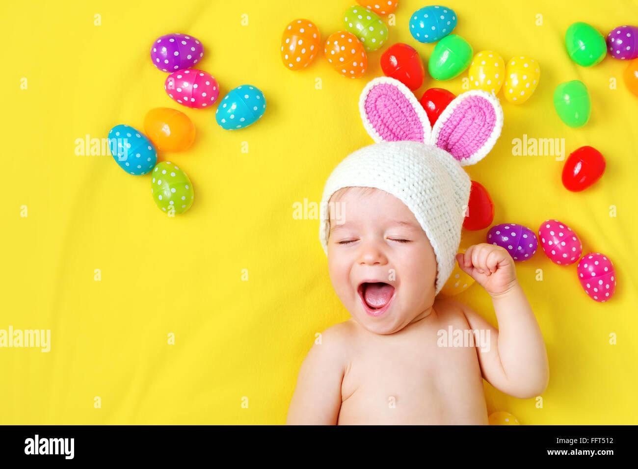 Baby Boy in Hase Hut liegen auf gelbe Decke mit Ostereiern Stockbild