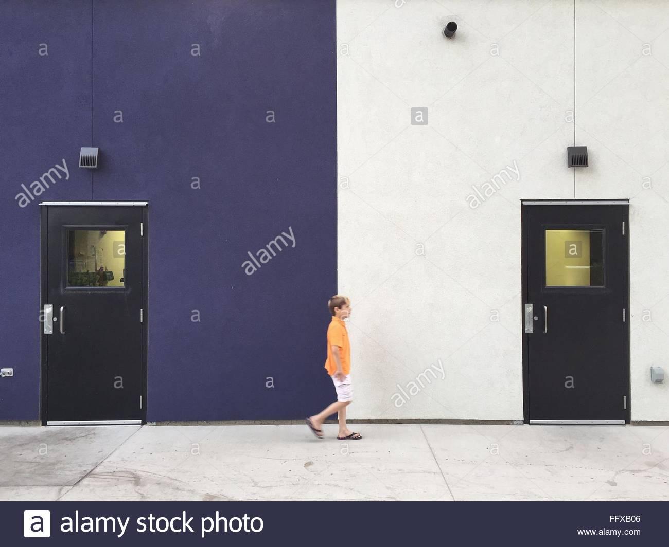 Voller Länge des jungen zu Fuß gegen Gebäude Stockbild