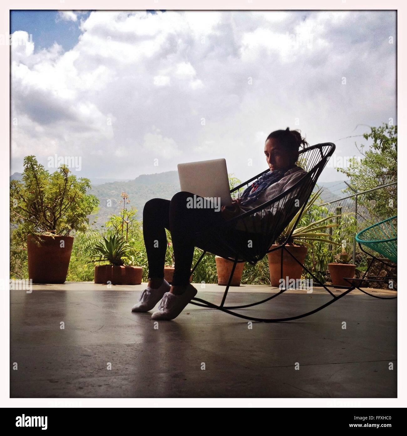 Frau arbeitet auf Laptop gegen bewölktem Himmel Stockbild