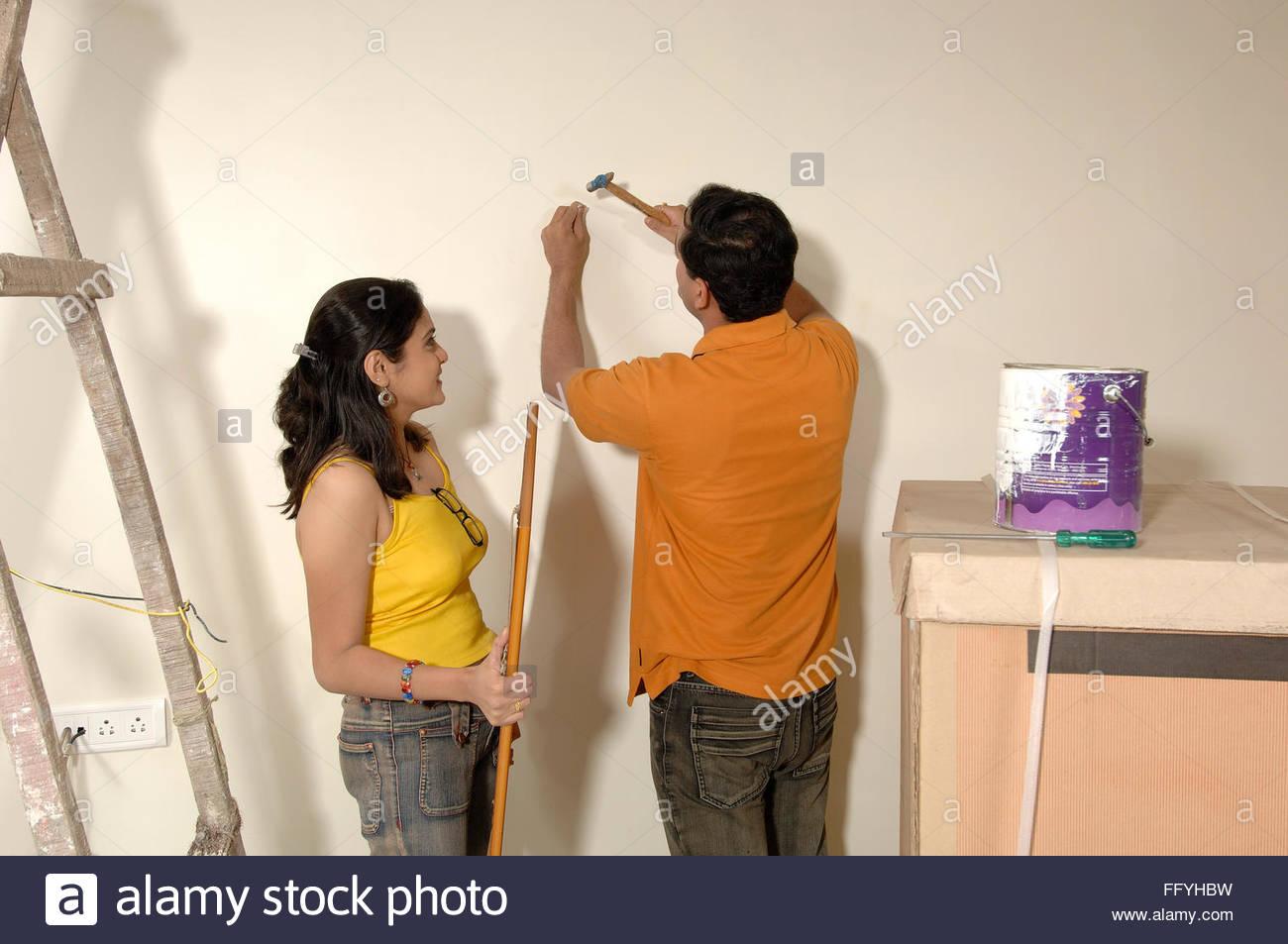 South Asian indischen Mann Hämmern Nagel auf Wand und Frau mit ...