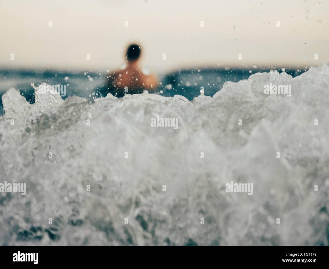 Nahaufnahme der Welle mit unscharfen Mann im Abstand Stockbild