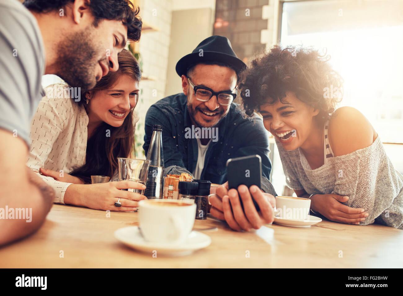 Porträt von fröhlichen jungen Freunden Smartphone betrachten, während Sie im Café sitzen. Gemischte Stockbild