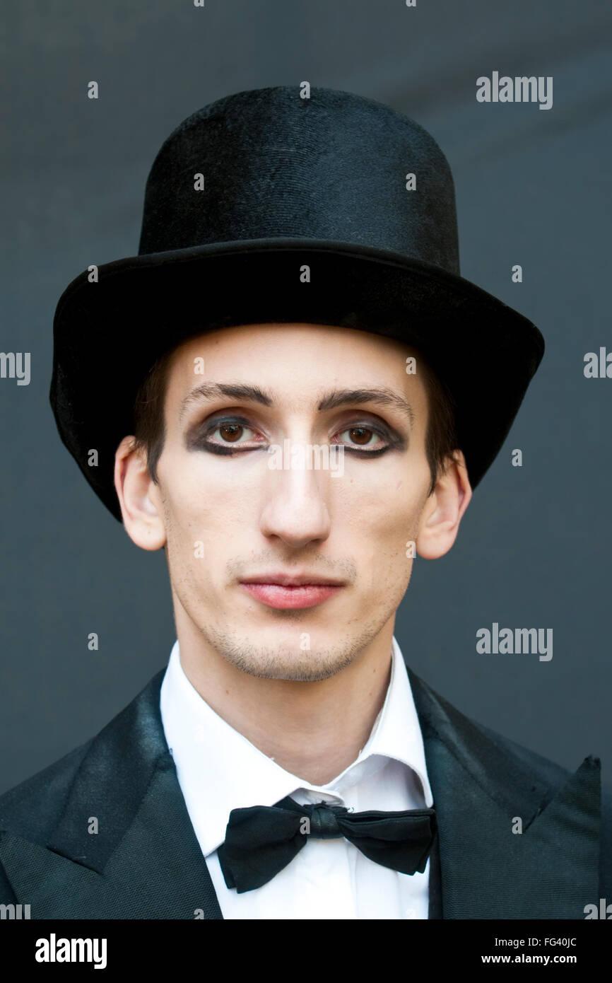 Ein Mann mit schweren Augen Make-up, gekleidet wie ein Zirkusdirektor in einem Zylinder und Fliege Stockbild