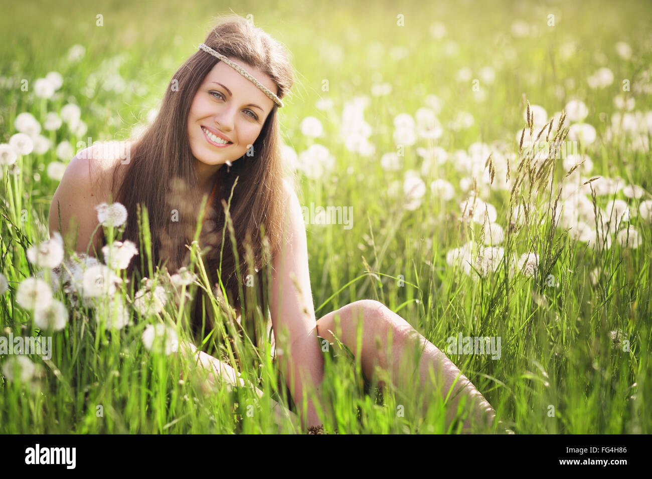 Schöne junge Frau lächelnd auf einer blühenden Wiese. Natur-Harmonie und Gelassenheit Stockbild