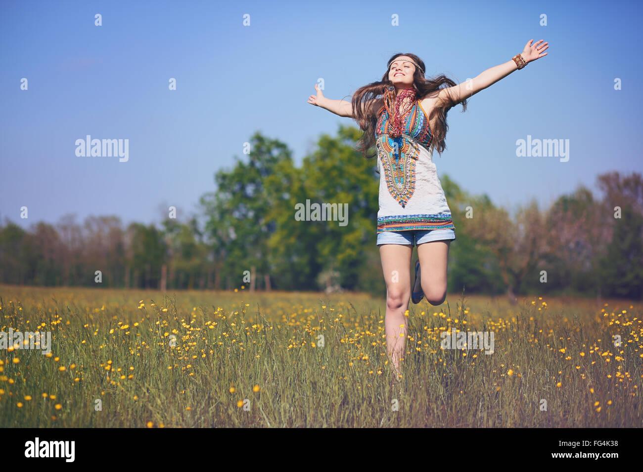 Glücklich und lächelnd Hippie-Frau springt in eine Sommerwiese. Vintage Photo-Effekt Stockbild