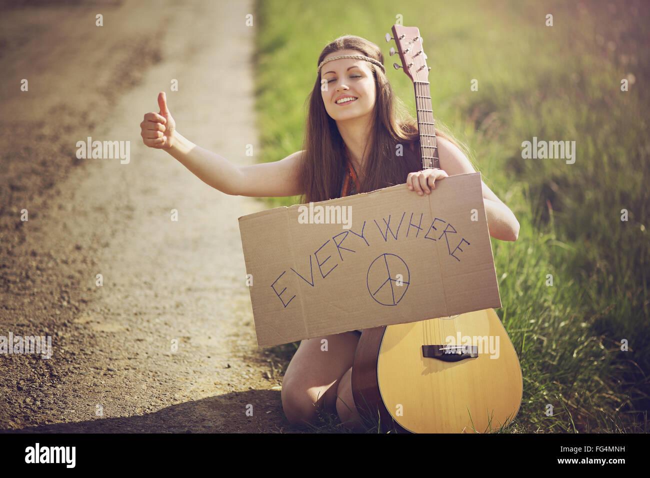 Hippie-Frau auf einer Landstraße Trampen. Reisen und Freiheit Stockbild