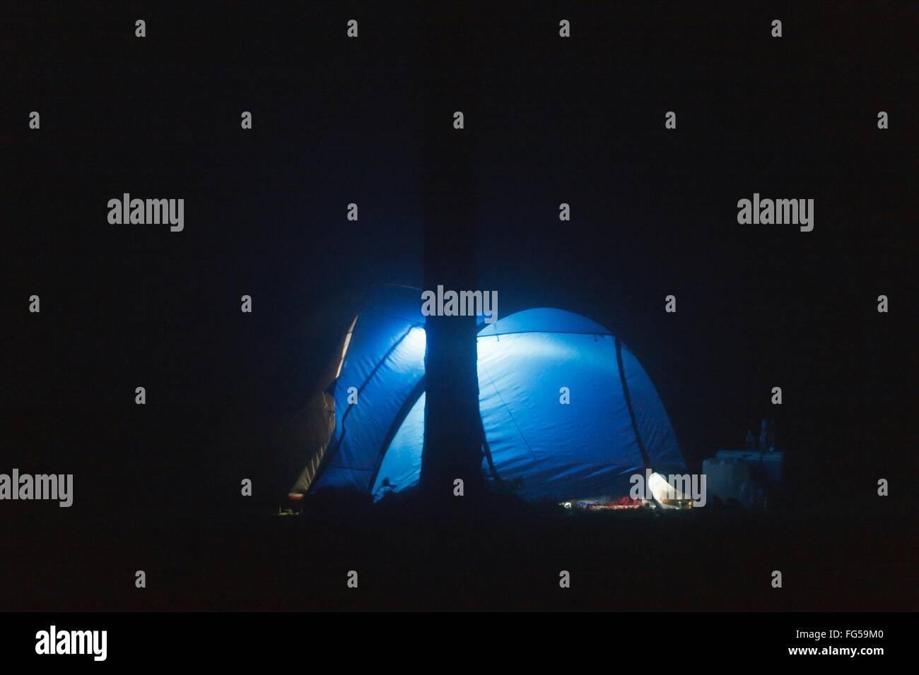 Blau beleuchtete Kuppelzelt auf Feld in der Nacht Stockbild