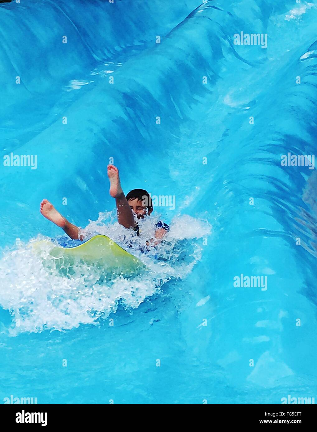 Junge auf Wasserrutsche Stockbild