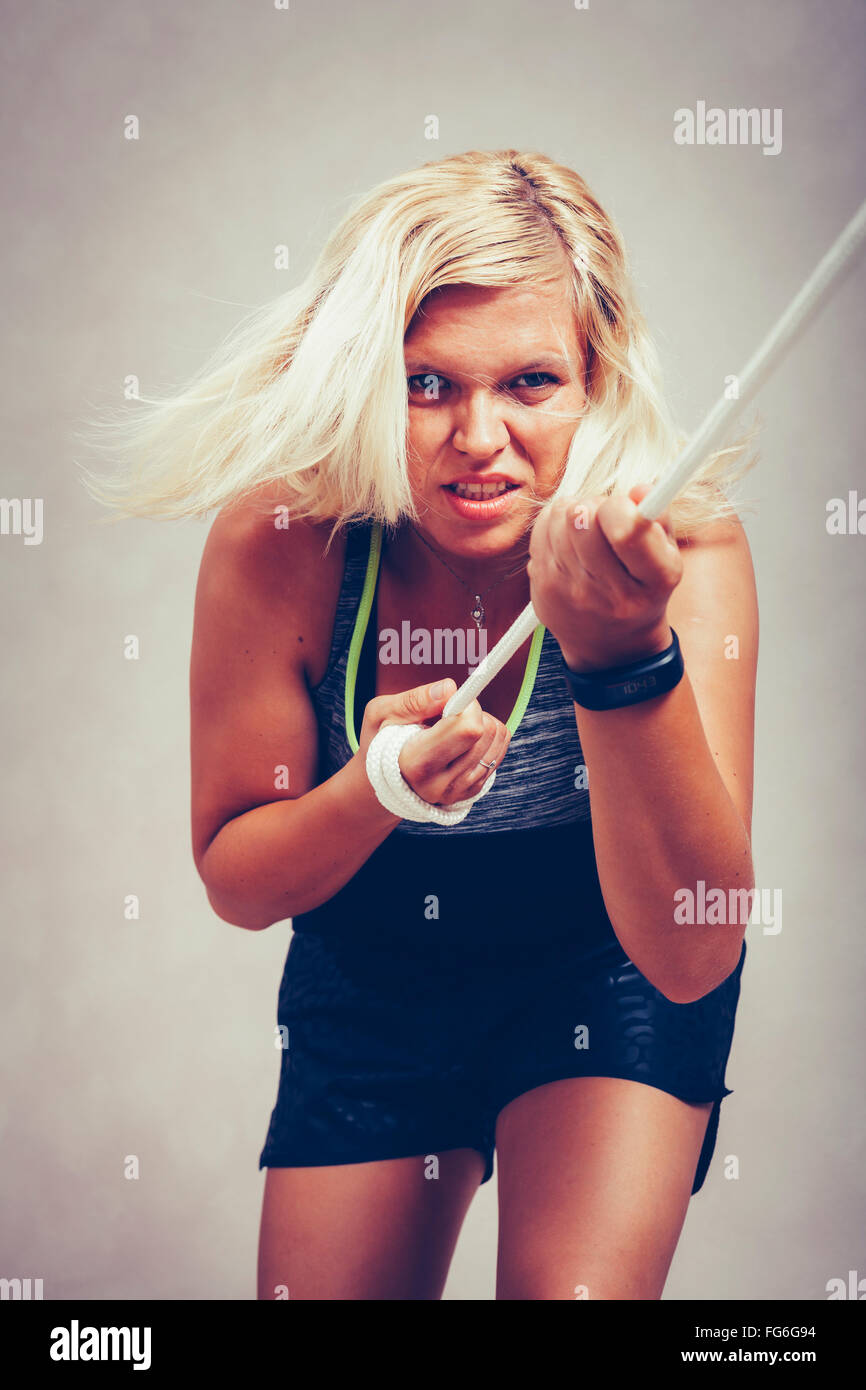 Selbstbewusste starke sportliche Frau ziehen das Seil. Entschlossenheit, Anstrengung und weibliche Power-Konzept. Stockbild