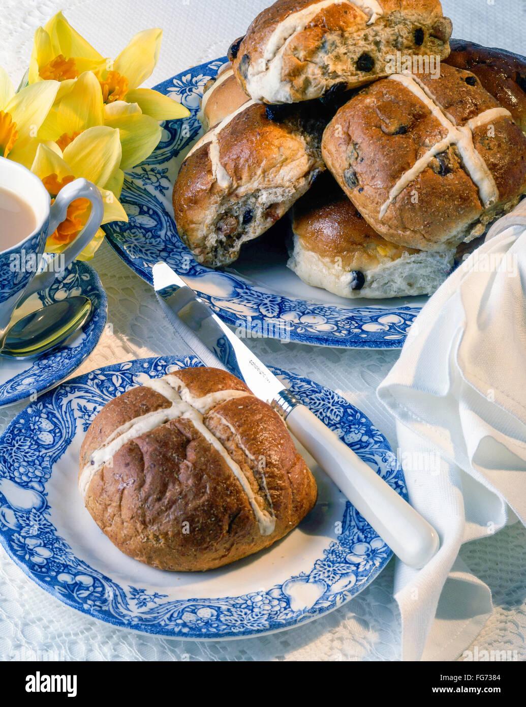 Hot Cross Buns auf Teller mit Messer und Tee in Studioumgebung Stockbild