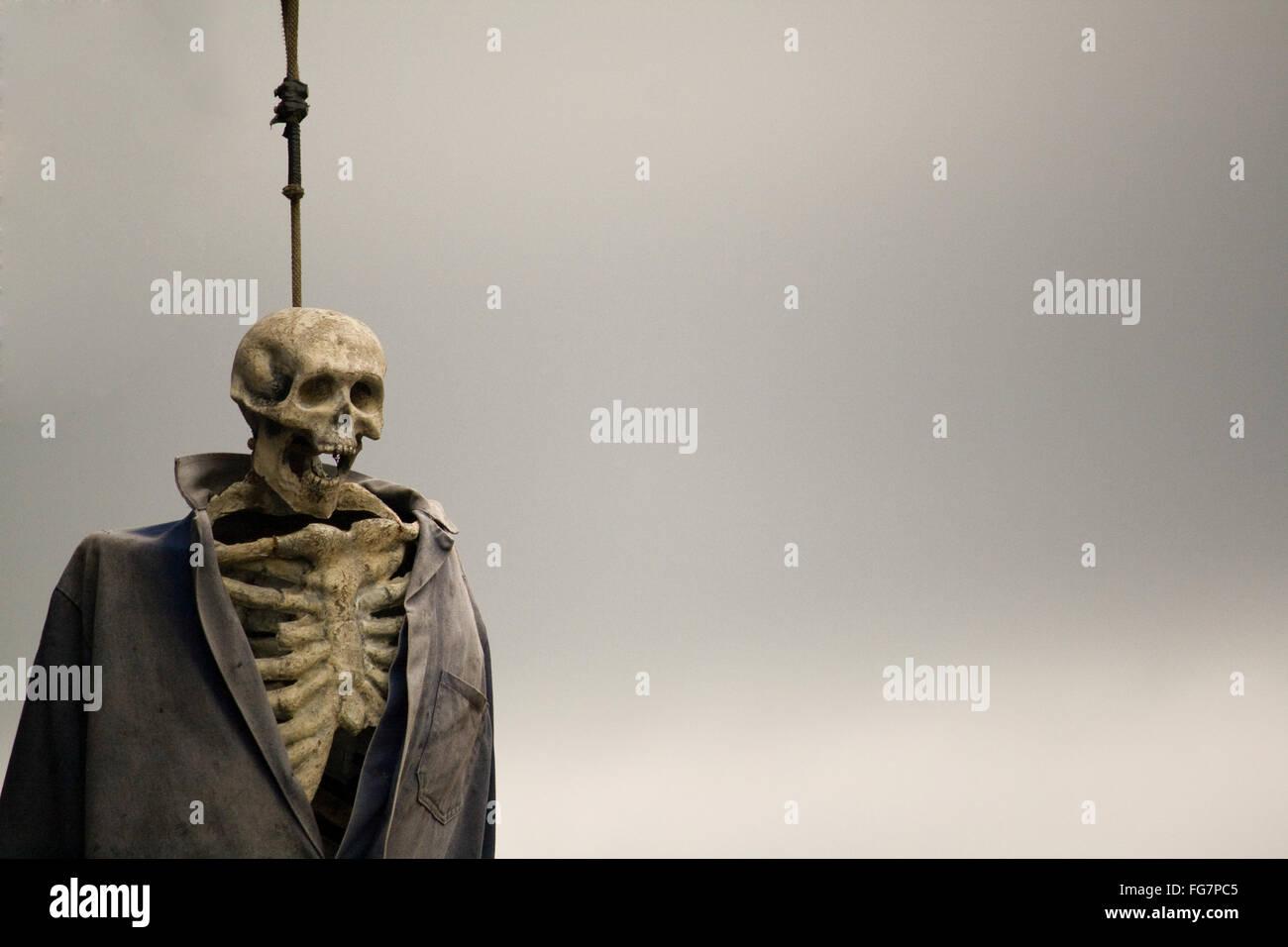 Menschliches Skelett hängend am Seil gegen Himmel Stockbild