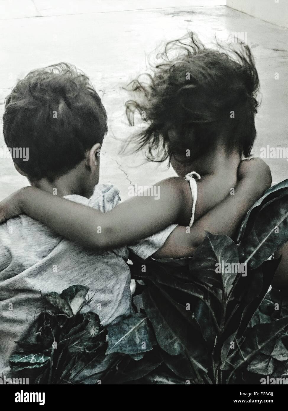Rückansicht der Geschwister mit Arm um im freien Stockbild