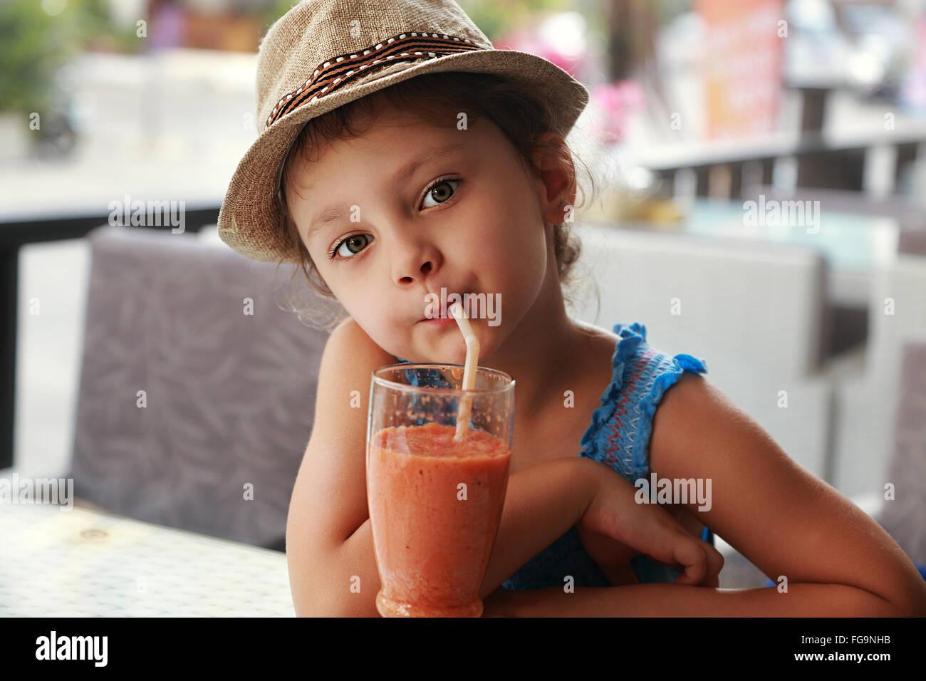Spaß süßes Kind Mädchen in Straße Restaurant gesunde Smoothie-Saft zu trinken. Closeup Stockbild