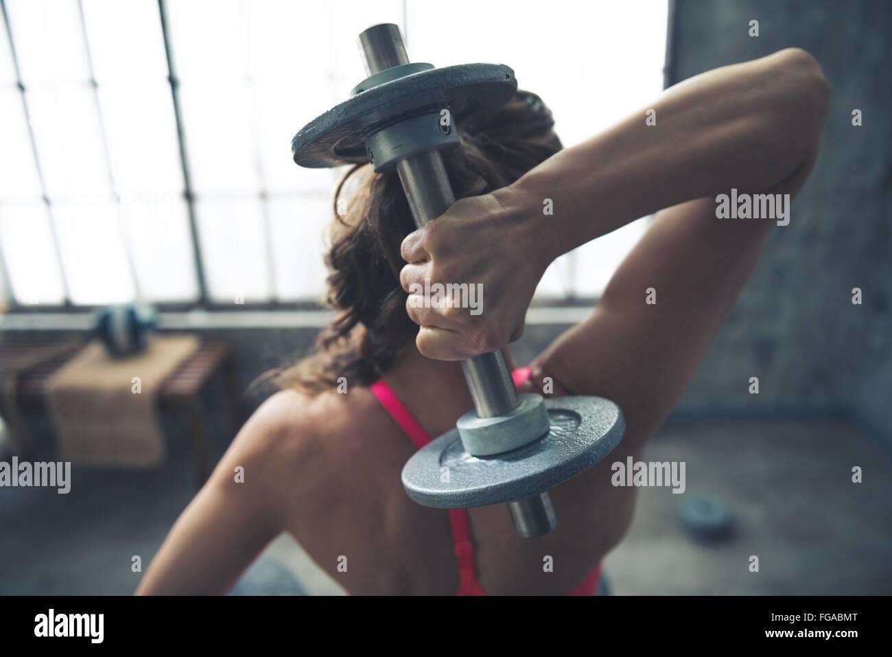 Körper und Geist im Loft-Fitness-Studio trainieren. Gesehen von hinten Fitness Frau Hantel heben Stockbild