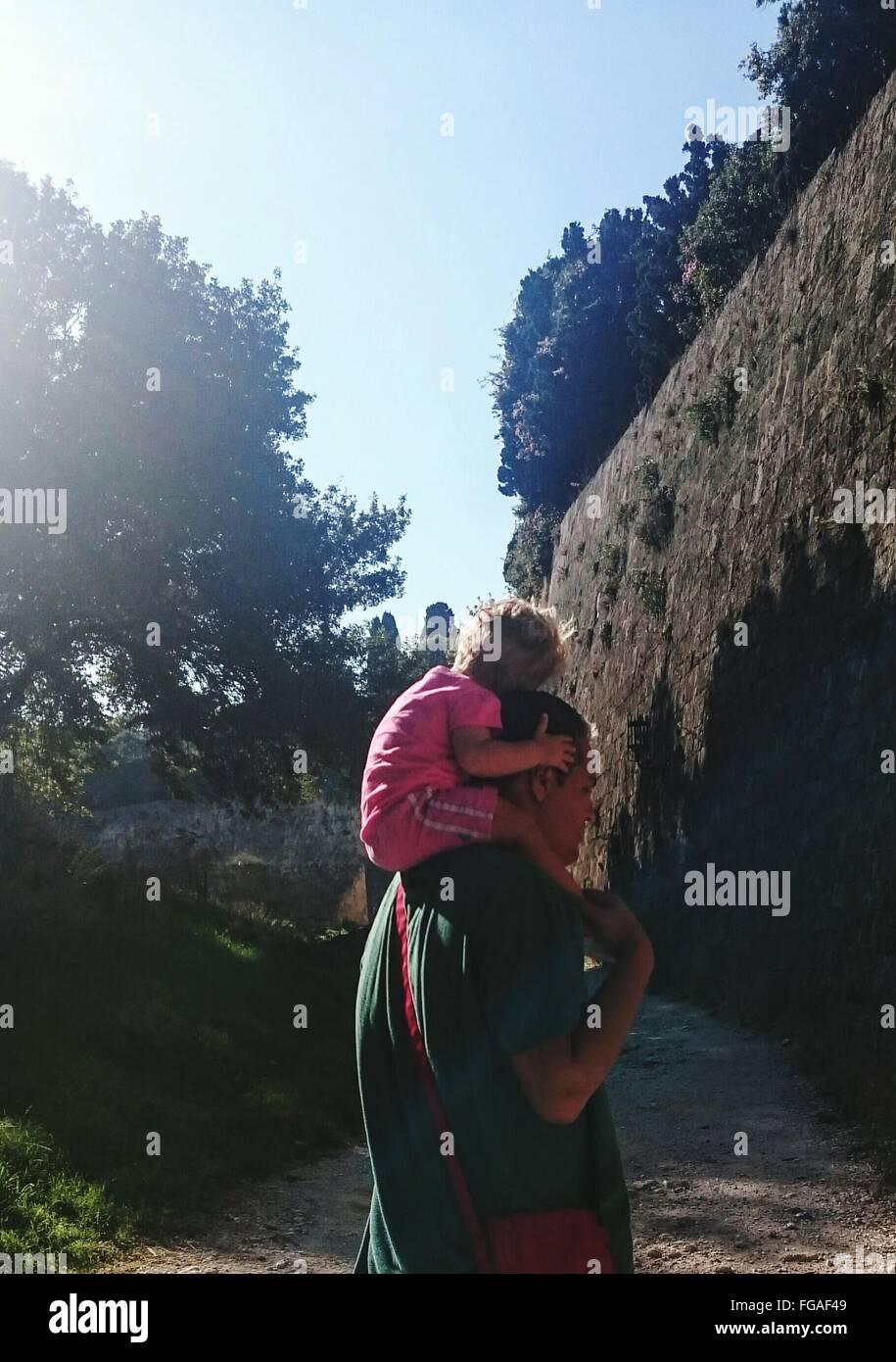 Vater mit Kind auf Schulter durch Mauer gegen Himmel Stockbild
