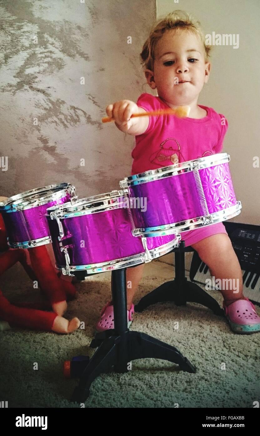 Niedliche Mädchen spielen Trommel zu Hause Stockbild