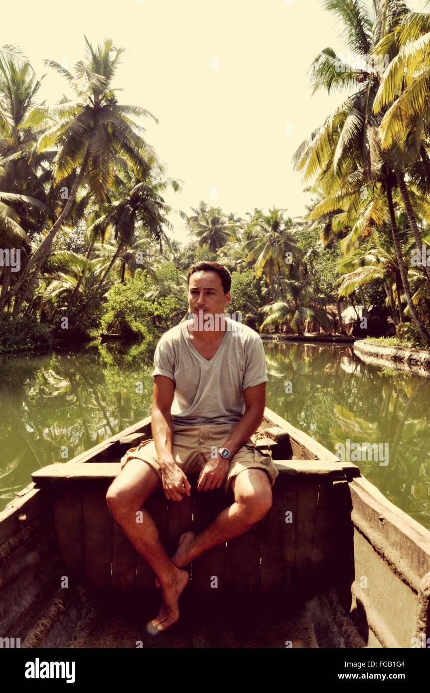 Junge Frau sitzt im Boot gegen Himmel Stockbild