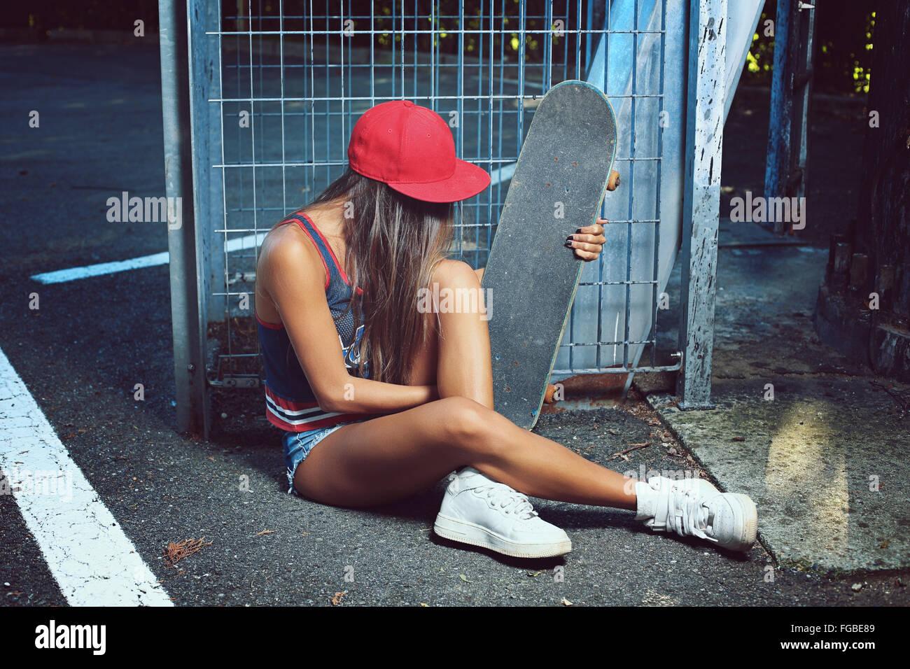 Skater-Girl auf der Straße sitzen. Städtischen Schuss Stockbild