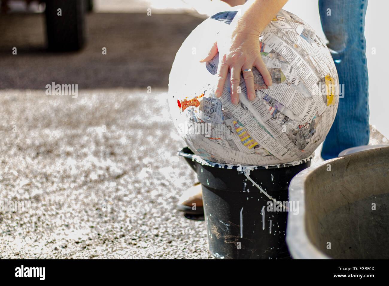 Bild von Hand berühren Papier Pappmaché-Kugel auf Eimer beschnitten Stockbild