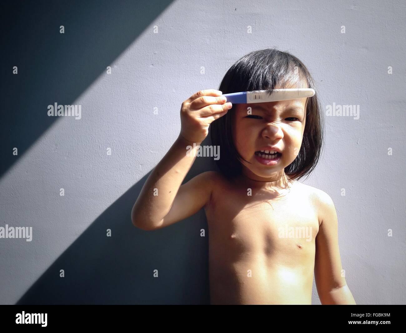 Porträt von Topless Girl Holding Schwangerschaftstest Stand gegen die Wand Stockfoto
