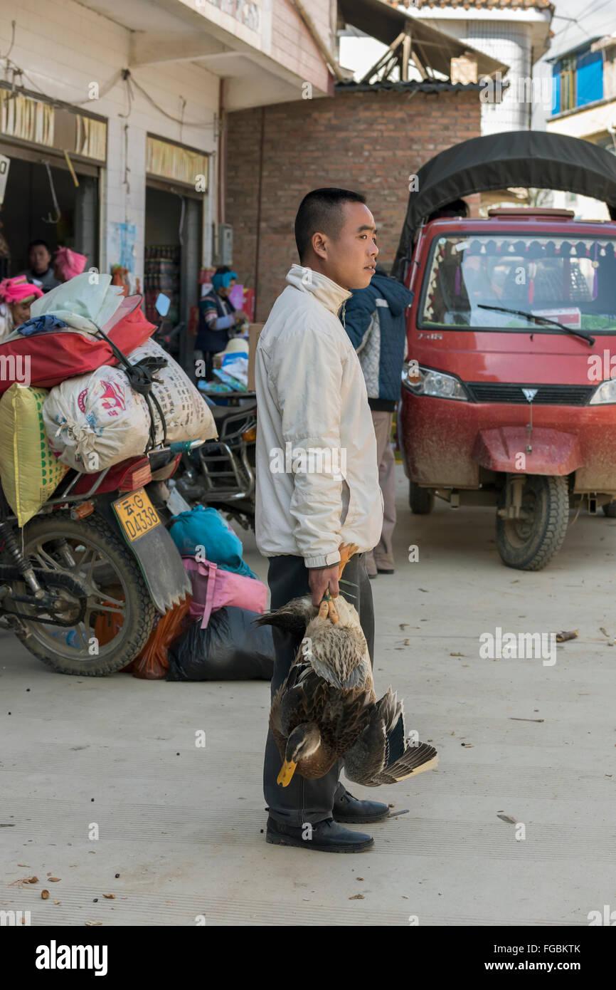Mann mit einer Ente, Niujiaozhai Markt, Provinz Yunnan, China Stockfoto